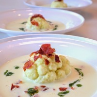 Cauliflower soup with bacon bits and ramson